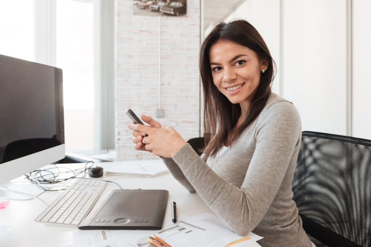 Cheerful businesswoman using computer and phone